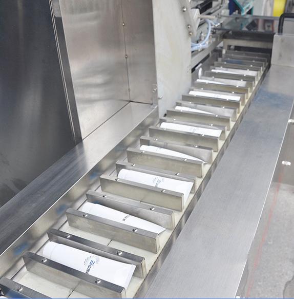 Infeed conveyor system of intermittent motion cartoner